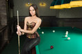 Sexy girl in corset plays billiards russian pyramid Royalty Free Stock Images