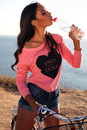 Sexy girl with dark hair drinking water sitting on bicycle Royalty Free Stock Photo