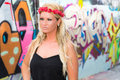 Sexy girl with flower headband and graffiti blonde woman fashion model wearing a black top red in urban setting long blonde hair Stock Image