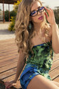 Sexy girl with long blond hair in glasses posing on beach fashion photo of beautiful glamour model curly and colorful dress Royalty Free Stock Images