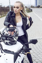 Sexy girl with long blond hair in leather jacket,posing on motorbike Royalty Free Stock Photo