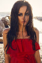 Sexy girl with long wet hair in elegant red dress posing on beach fashion photo of glamour model dark sea background Stock Photography
