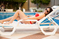 Sexy girl in a poolside chair cute young woman wearing bikini and sunglasses relaxing on Stock Photography