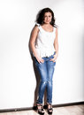 Sexy girl in singlet and jeans holding hands pockets Stock Photo
