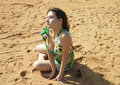 Sexy girl is sitting on the sand in green dress Royalty Free Stock Photo