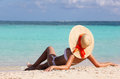 Sexy girl on tropical beach vacation woman in sun hat tanning and relaxing Royalty Free Stock Photos