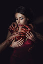 Sexy girl vampire in passionate embrace man s hands stained with blood the in a red dress a fashionable toning creative color Stock Image