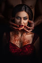 Sexy girl vampire in passionate embrace man s hands stained with blood the in a red dress a fashionable toning creative color Royalty Free Stock Photos