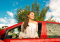 Sexy girl wearing a white blouse is coming out through the window of her red car in a beautiful sunny day Royalty Free Stock Photo