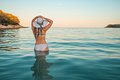 Sexy girl in white swimsuit with hat looking at sea at twilight with full moon and island in background Royalty Free Stock Photo