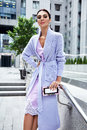 Sexy glamour woman in lilac fashion style dress with handbag Royalty Free Stock Photo