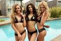 Sexy gorgeous women in elegant bikini  posing beside swimming pool Royalty Free Stock Photo