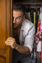 Sexy handsome young man hiding and peering out of a closet Royalty Free Stock Photo