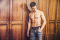 Sexy handsome young man standing shirtless against wardrobe Royalty Free Stock Photo