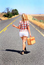 Sexy hitch hiker thumbing it a blonde beauty wearing shorts is hitching a ride with a suitcase on a desolate country road Royalty Free Stock Images