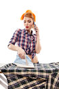 Sexy housewife talking to the phone while ironing isolated over white background Royalty Free Stock Photos