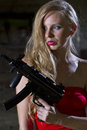 Sexy killer female spy in red dress with automatic gun Royalty Free Stock Image