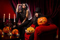 Sexy ladies vampire halloween concept with halloween pumpkins over red background Stock Images