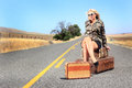 Sexy lady with baggage a blonde beauty wearing shorts and a camo shirt is waiting for a ride her on a desolate country road Stock Images