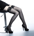 Sexy legs of a young and fit woman sitting in black stockings on a bar chair the image is taken on a light background Royalty Free Stock Photography