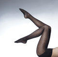 Sexy legs of a young and fit woman sitting in black stockings the image is taken on a light background Royalty Free Stock Photo