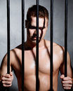Sexy man behind iron prison bars a Stock Photo