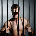 Sexy man behind iron prison bars with glasses a Royalty Free Stock Image