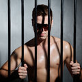Sexy man behind iron prison bars with glasses a Stock Images