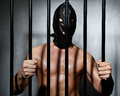 Sexy man behind iron prison bars with leather mask a Royalty Free Stock Photos