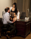 Sexy manager and woman at the office very beautiful women in lingerie is sitting on a desk is working late with her Royalty Free Stock Photos