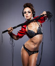 Sexy mistress in headphone and whip in erotic pose Royalty Free Stock Images