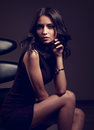 Sexy model in brown dress sitting on the black chair on dark dee Royalty Free Stock Photo