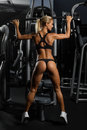 Sexy, muscular young woman in underwear posing against gym, full body figure Royalty Free Stock Photo