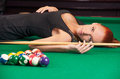 Sexy pool player beautiful young female in black dress lying on the billiard table and looking at camera Royalty Free Stock Images
