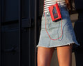 Sexy of pretty young sport style woman posing on vacation on the street having fun with vintage red cassette player Royalty Free Stock Photo