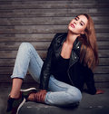 Sexy red hair woman posing in black jacket and blue jeans on str Royalty Free Stock Photo