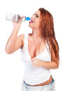 Sexy red hair woman in wet white t shirt drinking water Stock Photos