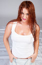 Sexy red hair woman in wet white t shirt over grey background Stock Photo