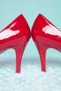 Sexy red pumps a pair of patent leather sit atop a white and teal fur surface with a teal background vintage colortones Stock Photography
