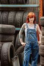 Sexy redhead mechanic with tattoos photo of a young beautiful wearing overalls and standing in an old garage attached property Stock Photos