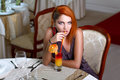 Sexy redhead woman drinking juice in restaurant indoor Stock Images
