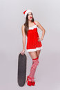 Sexy santa woman posing with skateboard Royalty Free Stock Photo