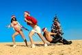 Santas pulling Santa at the beach Royalty Free Stock Photo