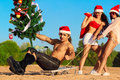 Sexy Santas  pulling Santa at the beach Royalty Free Stock Photos