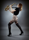 Sexy saxophonist young woman singing at saxophone full length Stock Photos
