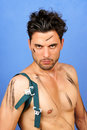 Sexy shirtless greasy worker year old caucasian looking at camera over a blue background Royalty Free Stock Image