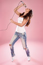 Sexy singer holding a microphone wearing white top and jeans Royalty Free Stock Photos
