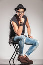 Sexy smiling fashion man is sitting on a chair Royalty Free Stock Photo