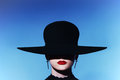 The sexy strict woman with red lips in a hat. Close-up Portrait