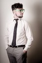 Sexy stylish businessman adjusting tie on gray background Royalty Free Stock Images